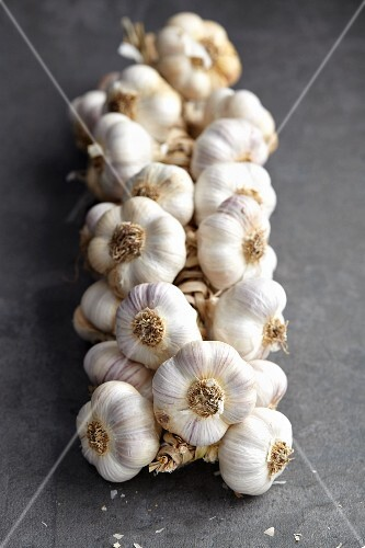 A string of garlic bulbs on a grey surface