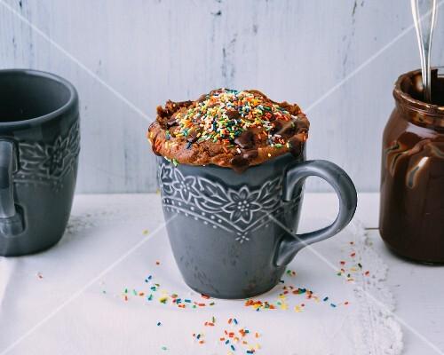A nut nougat mug cake with coloured sprinkles
