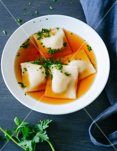 Gluten-free Swabian ravioli filled with vegetables and sausage meat swimming in meat broth