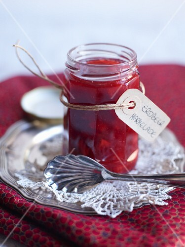 A jar of strawberry jam with a tag