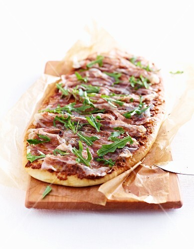 Pizza with pancetta and rocket on a wooden board