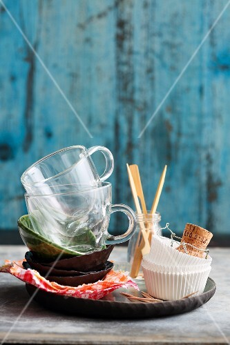 A stack of bowls, glass cups, paper cases and skewers on a tray