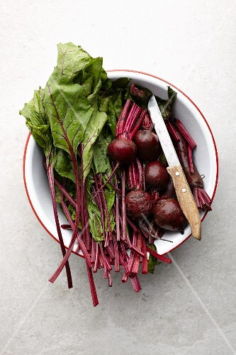 Beetroot leaves and beetroots in a bowl (seen from above)