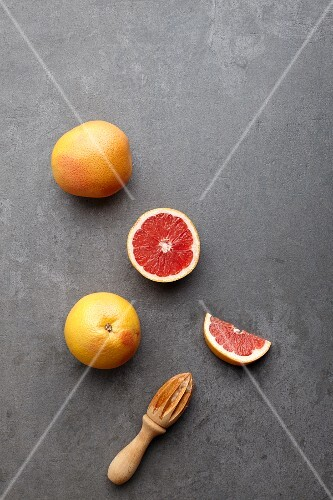 Pink grapefruits, whole and halved, with a wooden juicer (seen from above)