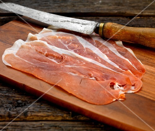 Slices of Parma ham on a wooden chopping board