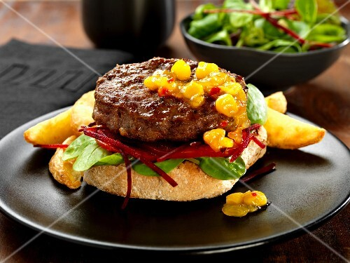 Beef and Stilton burger with a sweetcorn relish and salad on a ciabatta roll