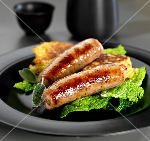 Pork and herb sausages with Savoy cabbage and potato fritters