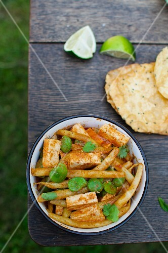 Vegan Thai curry with tofu, beans, poppadoms and limes