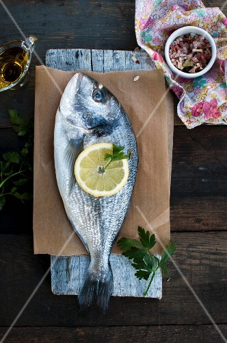 Gilt head seabream with olive oil, lemon slices, parsley and Himalayan salt