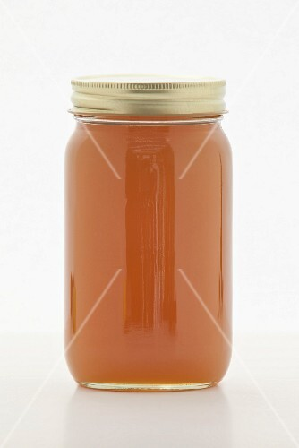 Brown rice syrup as sugar replacement in a screw-top jar on a white surface