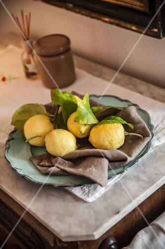 An arrangement of lemons on a grey linen napkin