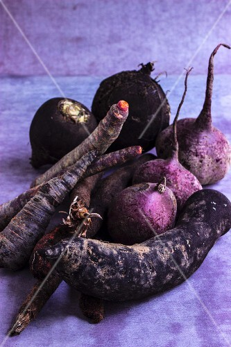 Dark root vegetables on a grey surface