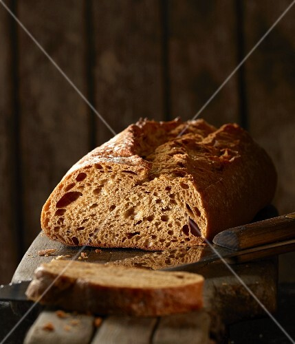 Wholemeal baguette on a wooden board with a knife, sliced
