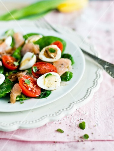 Spinach salad with smoked salmon, tomatoes and quail's eggs