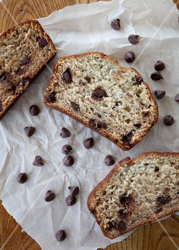 Three slices of banana bread with chocolate chips on a piece of parchment paper