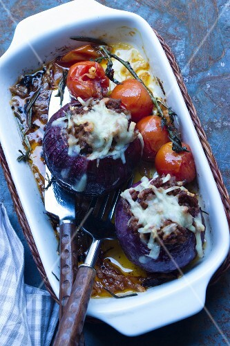 Stuffed red onions gratinated with Parmesan with braised vine tomatoes in a baking dish