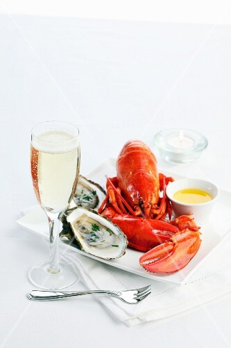 Cooked lobster with butter and oysters on a serving platter with champagne