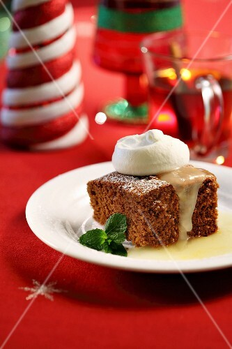 A slice of spiced cake with vanilla sauce and cream for Christmas