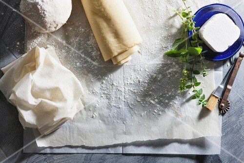Filo pastry and cheese on baking paper for making burekas