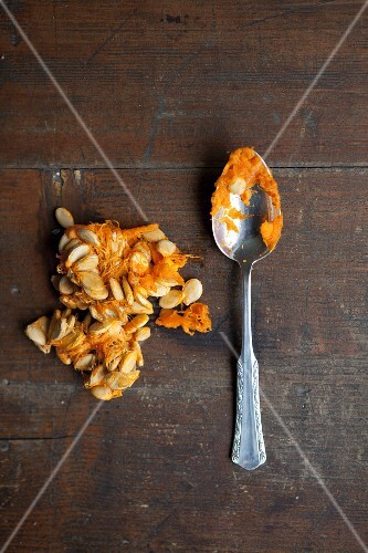 Pumpkin seeds on a wooden table with a spoon