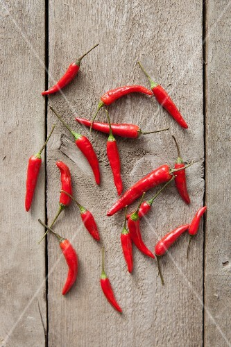 Fresh red chilli peppers on a wooden table (seen from above)