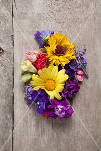 Various summer flowers on a wooden table (seen from above)