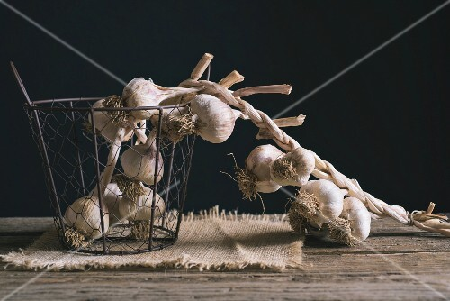 A string of garlic in a wire basket on a wooden table