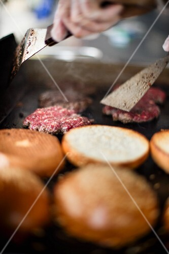 Beefburgers being fried next to toasted buns