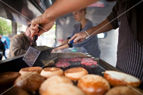 Beefburgers being fried next to halved rolls in a fast food truck