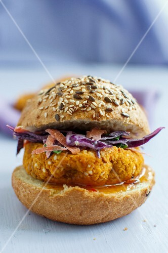 A vegan burger made from chickpeas, millet and sweet potatoes on a wholemeal roll with red cabbage salad and mango sauce