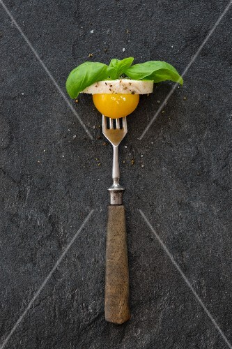 A yellow cherry tomato, a slice of the mozzarella and basil leaves on a fork