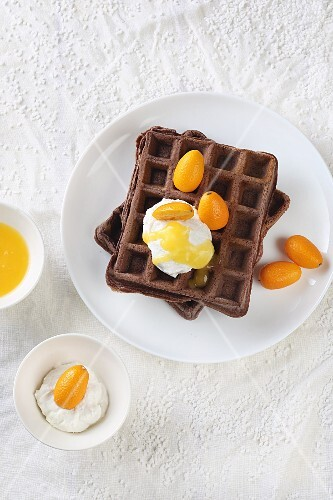 Cocoa waffles with orange sauce, ricotta and kumquats