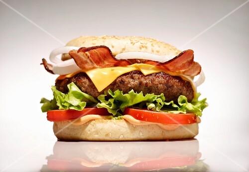 A bacon cheeseburger on a white surface