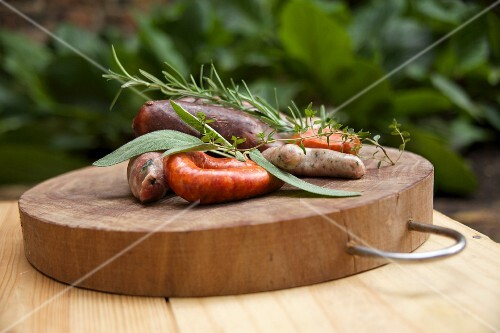 A wooden platter with various sausages and herbs
