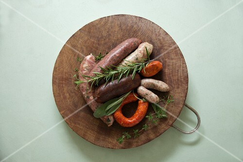 Various uncooked sausages and herbs on a wooden platter