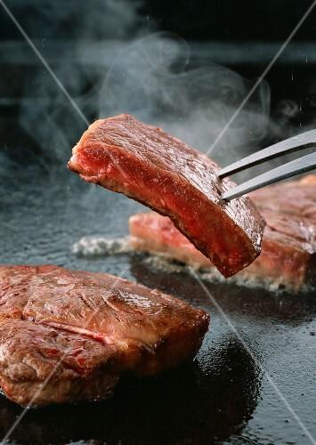 Sirloin steaks being fried