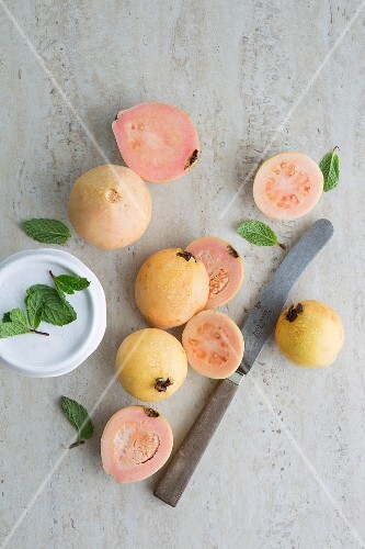 Guavas, whole and halved, on a grey surface