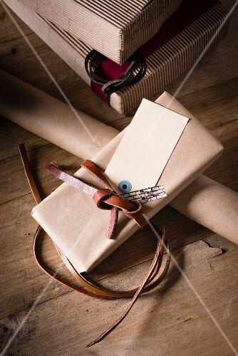 Geschenkschachteln, Geschenkpapier und verpacktes Geschenk mit Lederband auf Holztisch