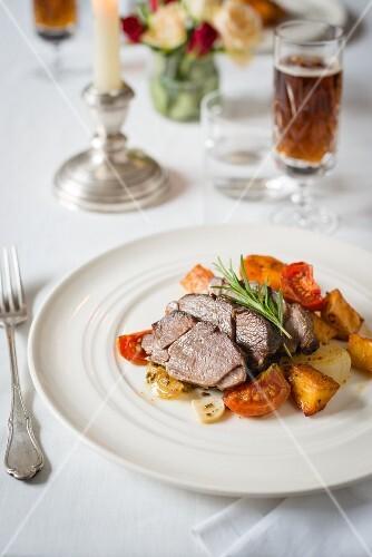 Roast lamb with roast potatoes and tomatoes