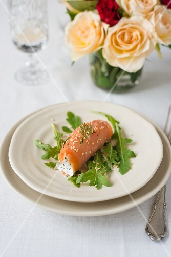 A smoked salmon roll with the yoghurt, sesame seeds and rocket