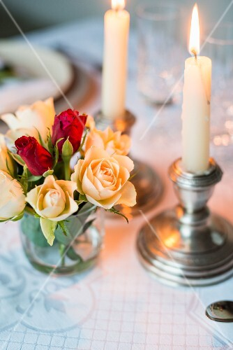 Candles and a bunch of roses as romantic table decoration
