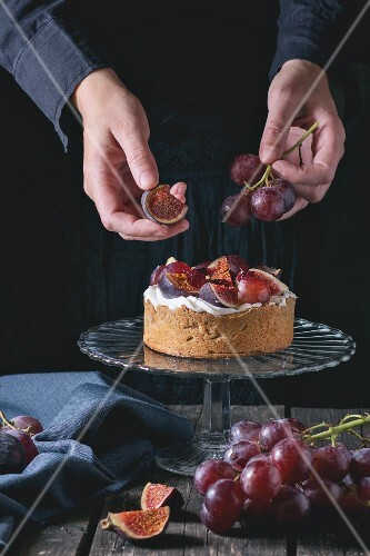A woman's hands decorating a homemade tart with red grapes, figs and whipped cream
