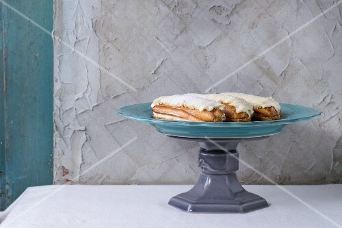 Homemade eclairs with white buttercream on retro turquoise cake stand