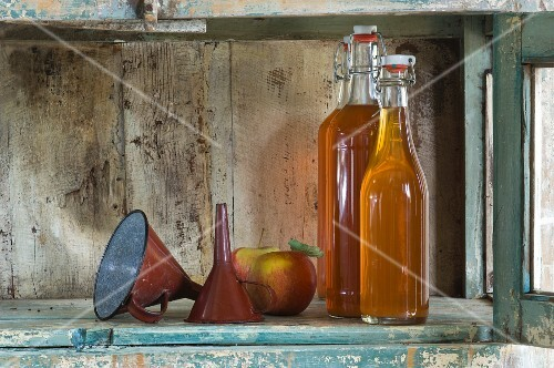 Bottles of apple juice, a funnel and Jonagold apples on a rustic shelf