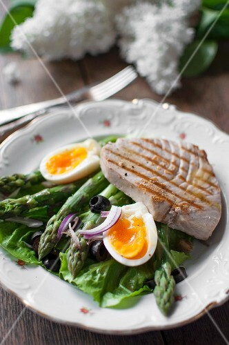 Salad Nicoise with lettuce, asparagus, egg, onions, black olives and tuna steak