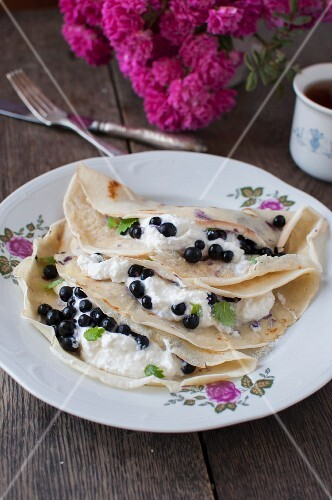Pancakes with quark and blueberries decorated with lemon balm