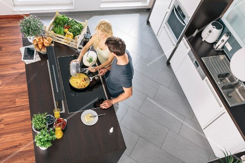 Couple cooking scrambled eggs in kitchen (top view)