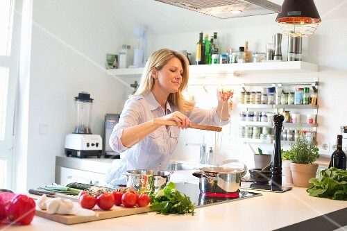 A woman cooking spaghetti in a modern kitchen