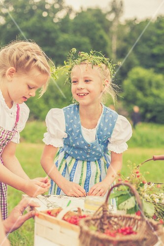 Little girls wearing dirndls and wreaths in their hair at a table outside