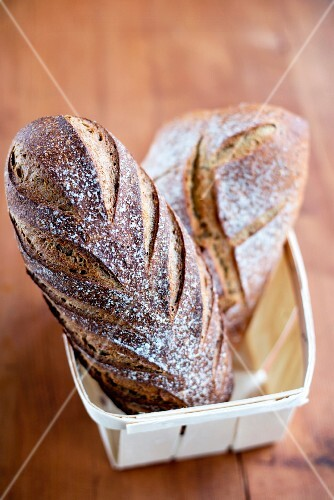 Two loaves of French bread in a wooden basket